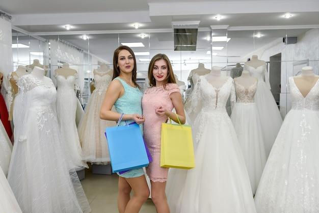 Aantrekkelijke vrienden met boodschappentassen in trouwsalon