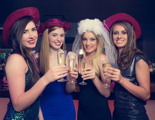 Aantrekkelijke vrienden rammelende champagneglazen bij kippenacht