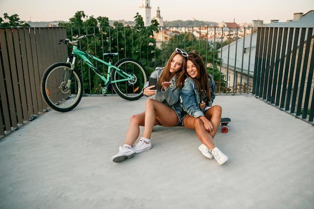 Aantrekkelijke vriendinnen die videogesprek voeren op smartphone en zich gelukkig voelen in het moderne stadspark.