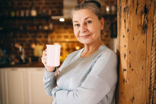 Aantrekkelijke vrolijke bejaarde vrouw poseren binnenshuis genieten van warme verse koffie uit de beker in de ochtend.
