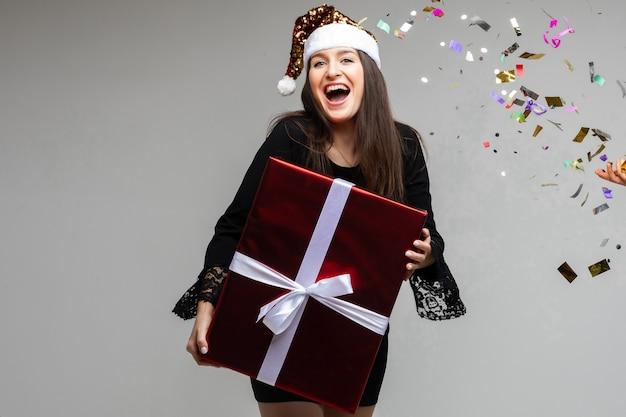 Aantrekkelijke vrolijke brunette vrouw in zwarte jurk en kerstmuts met grote verpakte kerstcadeau in handen. kleurrijke confetti aan de rechterkant.
