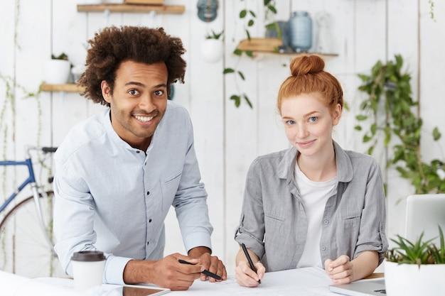 Aantrekkelijke vrolijke donkere ingenieur met afro-kapsel en zijn schattige roodharige vrouwelijke collega