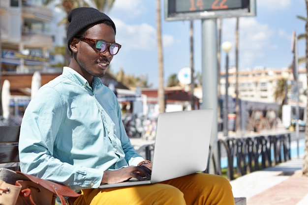 Aantrekkelijke vrolijke jonge afro-amerikaanse mannelijke freelancer gekleed in stijlvolle slijtage zittend op een stedelijke bank met laptopcomputer op schoot en met behulp van gratis draadloze internetverbinding voor werk op afstand