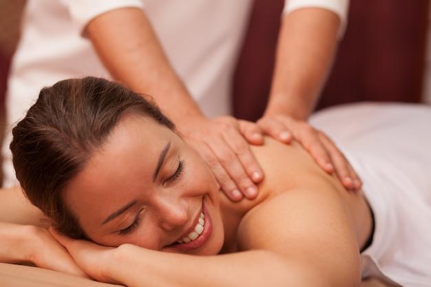 Aantrekkelijke vrolijke jonge vrouw die vrolijk glimlacht waarom professionele masseur haar schouder masseert. het schitterende vrouw ontspannen in day spa. therapeut kalmerende massage geven aan vrouwelijke cliënt. schoonheid