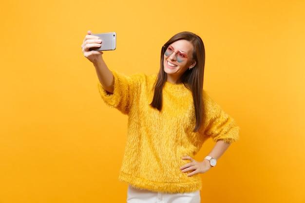Aantrekkelijke vrolijke jonge vrouw in bont trui, hart bril doen selfie schot op mobiele telefoon geïsoleerd op heldere gele achtergrond. mensen oprechte emoties, lifestyle concept. reclame gebied.