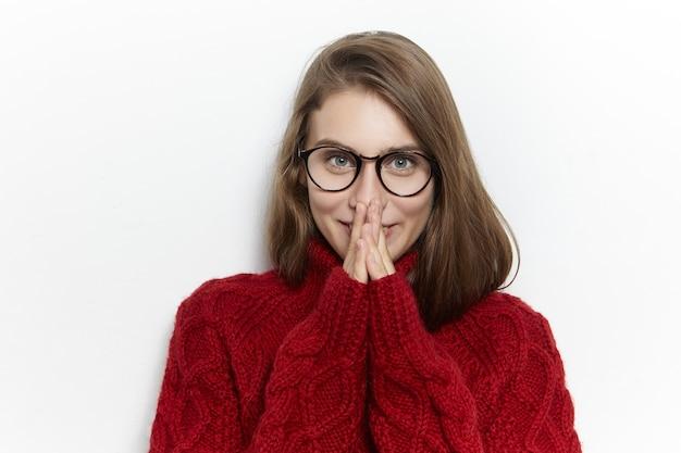 Aantrekkelijke vrolijke jonge vrouw in brillen en warme, gezellige trui met gevouwen handen naar haar gezicht en gelukkig lachend, opgewonden met aangenaam nieuws, cadeau, kijken