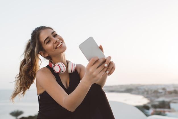 Aantrekkelijke vrolijke jonge vrouw in sportkleding glimlachen, chillen aan de kust. zonsopgang in de ochtend, modieus model, training, selfie maken, opgewekte stemming