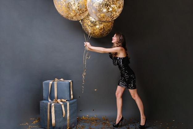 Aantrekkelijke vrolijke jonge vrouw in zwarte luxe jurk met plezier met grote ballonnen vol met gouden tinsels. gelukkige verjaardagspartij, cadeautjes, glimlachen, positiviteit uiten.
