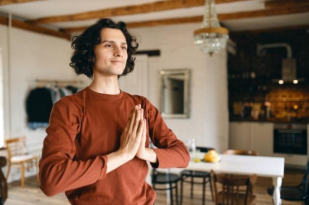 Aantrekkelijke vrolijke jongeman hand in hand tegen elkaar gedrukt op zijn borst dankbaarheid uiten, namaste gebaar maken