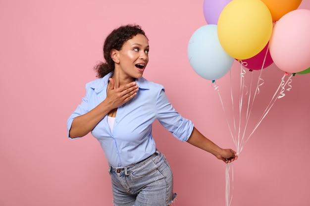 Aantrekkelijke vrolijke verrast vrouw van gemengd ras etniciteit kijkt naar veelkleurige heldere lucht ballonnen in haar handen, geïsoleerd op roze achtergrond met kopie ruimte voor tekst en reclame