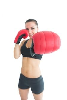 Aantrekkelijke vrolijke vrouw die rode bokshandschoenen draagt