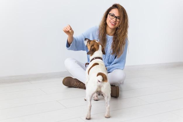 Aantrekkelijke vrolijke vrouw in blauwe trui spelen met haar favoriete huisdier