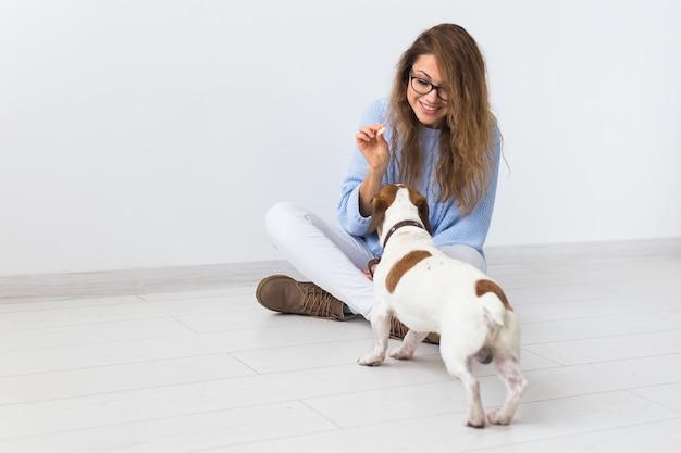 Aantrekkelijke vrolijke vrouw in blauwe trui spelen met haar huisdier