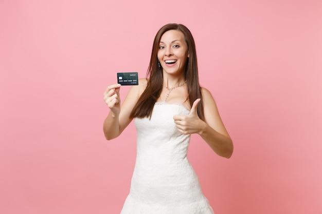 Aantrekkelijke vrolijke vrouw in witte jurk met creditcard die duim omhoog laat zien