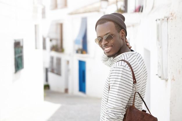Aantrekkelijke vrolijke zwarte europese toerist in tinten en hoed lopen op straten van buitenlandse stad tijdens vakanties in het buitenland. mensen, levensstijl, reizen, avontuur, toerisme en vakantie concept