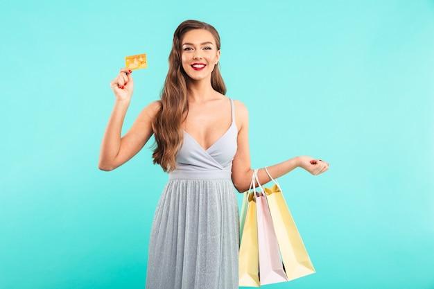 Aantrekkelijke vrouw 20s in jurk shopping pakketten te houden en gouden creditcard te tonen, geïsoleerd over blauwe muur
