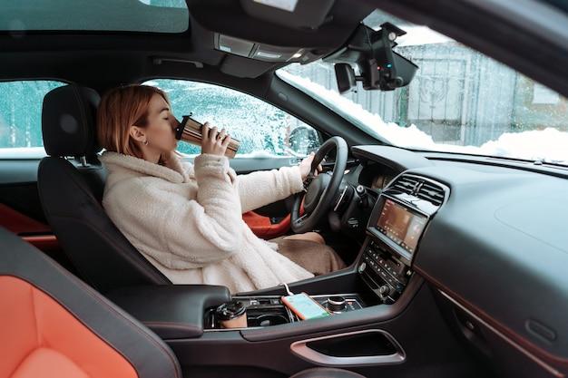 Aantrekkelijke vrouw bestuurder zitten achter het stuur in haar auto