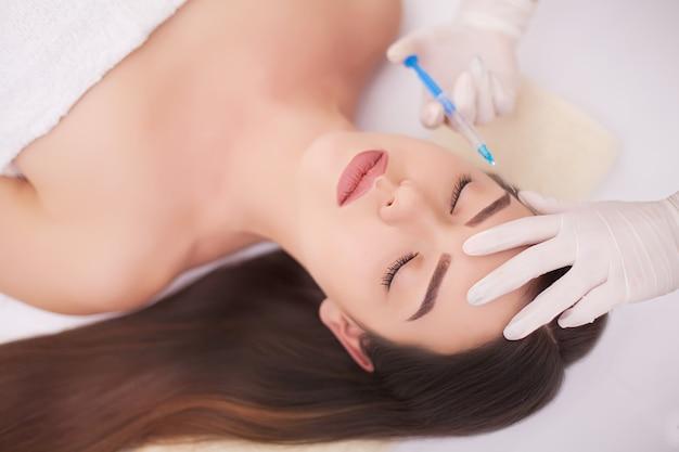 Aantrekkelijke vrouw bij plastische chirurgie met spuit in haar gezicht