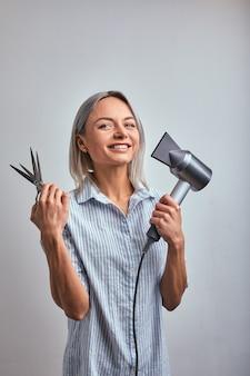 Aantrekkelijke vrouw blonde kapper met professionele tool poseren op camera, grijze achtergrond. kopieer ruimte, reclamebanner, schoonheidsconcept.