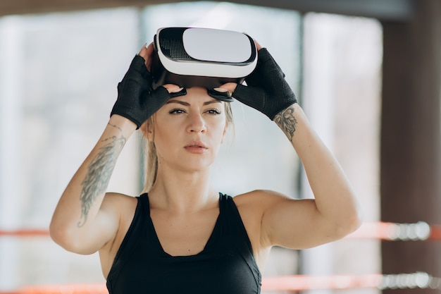 Aantrekkelijke vrouw boksen in vr 360 headset training voor schoppen in virtual reality