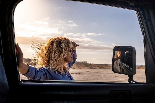 Aantrekkelijke vrouw buiten de auto kijkt naar de weg in avontuurlijke reizen vrijheid levensstijl volwassen vrouw