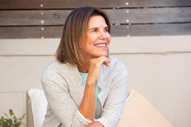 Aantrekkelijke vrouw buiten zitten en glimlachen