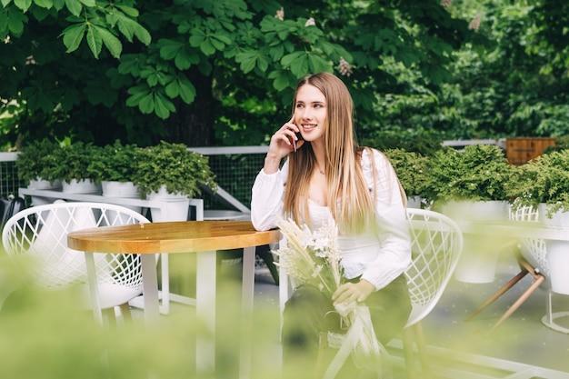 Aantrekkelijke vrouw die aan een tafel zit en naar de camera glimlacht en telefoon spreekt