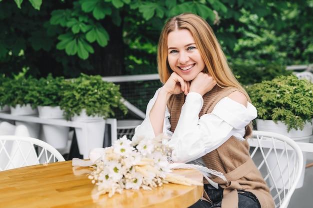 Aantrekkelijke vrouw die aan een tafel zit en naar de camera glimlacht