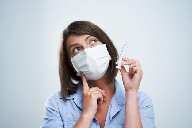 Aantrekkelijke vrouw die beschermend masker draagt dat over witte achtergrond wordt geïsoleerd