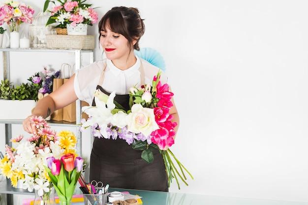 Aantrekkelijke vrouw die bloemen in bloemenwinkel schikt