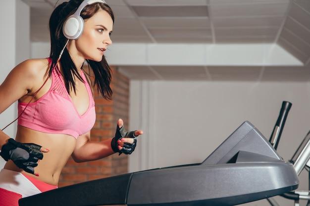 Aantrekkelijke vrouw die cardiooefeningen doet, die op tredmolens in de gymnastiek lopen
