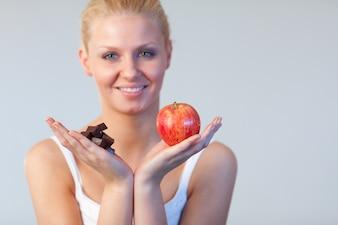 Aantrekkelijke vrouw die chocolade en appeldrocus op chocolade en appel toont