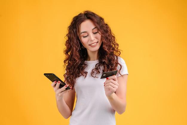 Aantrekkelijke vrouw die creditcard en telefoon gebruikt die gelijktijdig over gele achtergrond wordt geïsoleerd
