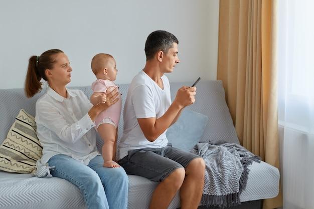 Aantrekkelijke vrouw die dochtertje in handen houdt, haar man achterover naar zijn familie zit en smartphone gebruikt, wil geen tijd doorbrengen met naaste mensen, surfen op internet of berichten typen.