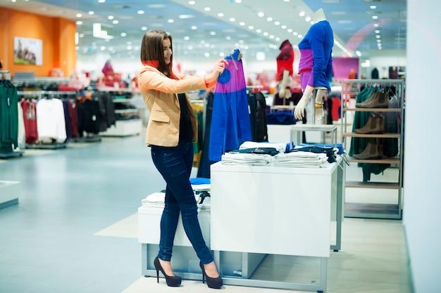 Aantrekkelijke vrouw die doeken in winkel kiest
