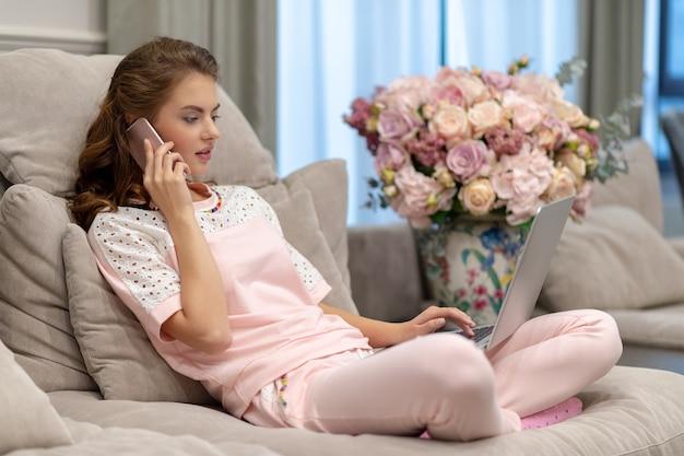 Aantrekkelijke vrouw die door slimme telefoon roept die aan computer werkt. jonge vrouw met mobiele telefoon en laptop.