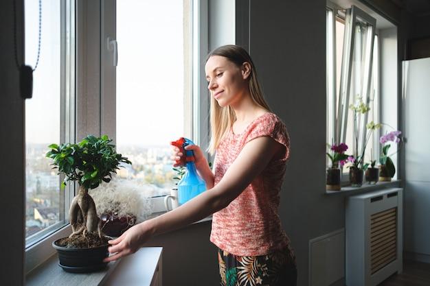 Aantrekkelijke vrouw die een bonsaiboom in het appartement water geeft