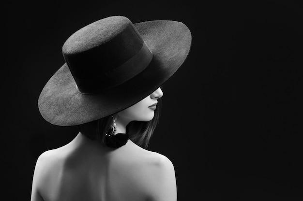 Aantrekkelijke vrouw die een hoed draagt die op zwarte achtergrond stelt