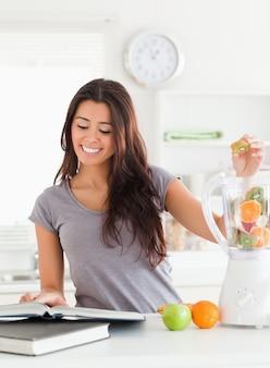 Aantrekkelijke vrouw die een notitieboekje raadpleegt terwijl het vullen van een mixer met vruchten