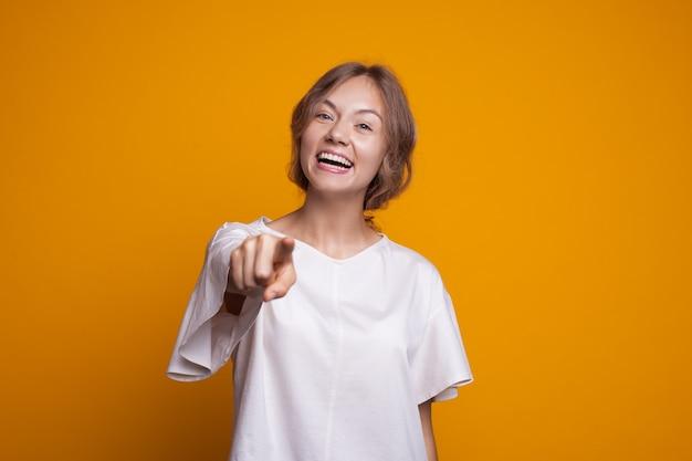 Aantrekkelijke vrouw die en op camera op een gele muur glimlacht richt die een wit t-shirt draagt