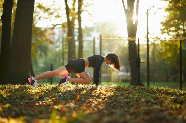 Aantrekkelijke vrouw die fysieke activiteit doet bij park