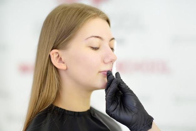 Aantrekkelijke vrouw die gezichtsverzorging krijgt bij schoonheidssalon.