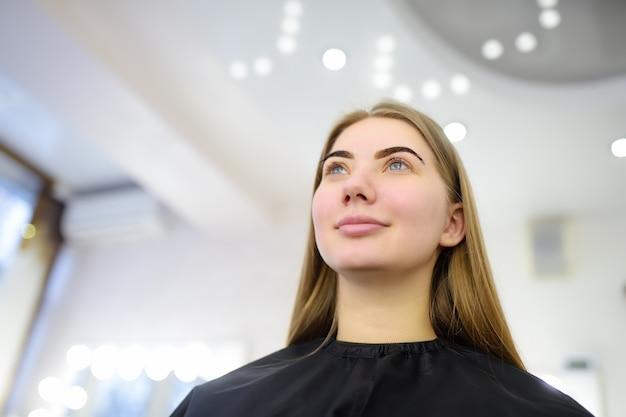 Aantrekkelijke vrouw die gezichtszorg krijgt bij schoonheidssalon. perfecte architectuurwenkbrauwen. gezichtsverzorging en make-up.