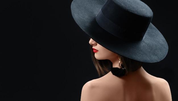 Aantrekkelijke vrouw die hoed het stellen op zwarte achtergrond draagt