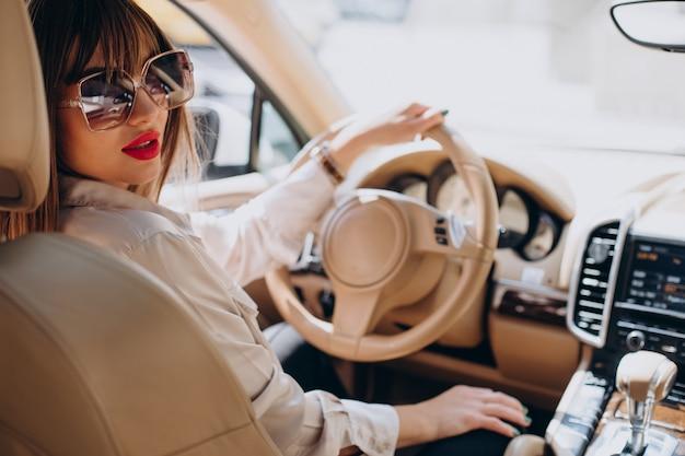 Aantrekkelijke vrouw die in haar auto zit