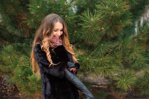 Aantrekkelijke vrouw die in het park in de herfstdag loopt