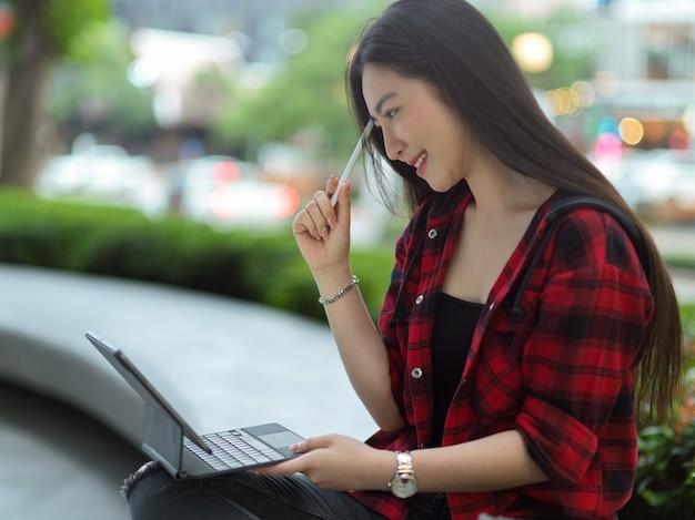 Aantrekkelijke vrouw die in het park zit en aan het werk denkt en ideeën vindt die buitenshuis op een draagbare tablet werken