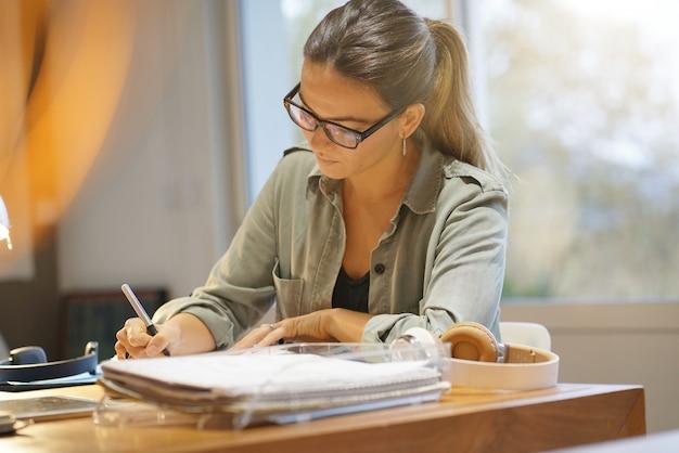 Aantrekkelijke vrouw die in mede werkende bureauruimte werkt