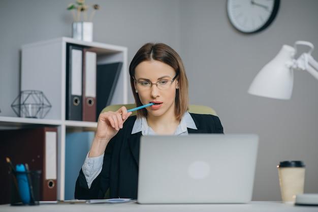 Aantrekkelijke vrouw die in oogglazen van haar favoriete freelance baan genieten die in huis aan laptop computer werken. vrouwelijke freelancer die netbook gebruikt en ideeën in blocnote schrijft