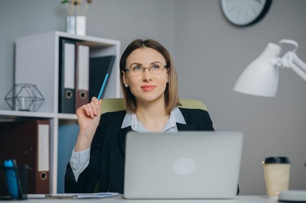 Aantrekkelijke vrouw die in oogglazen van haar favoriete freelance baan genieten die in huis aan laptop computer werken.